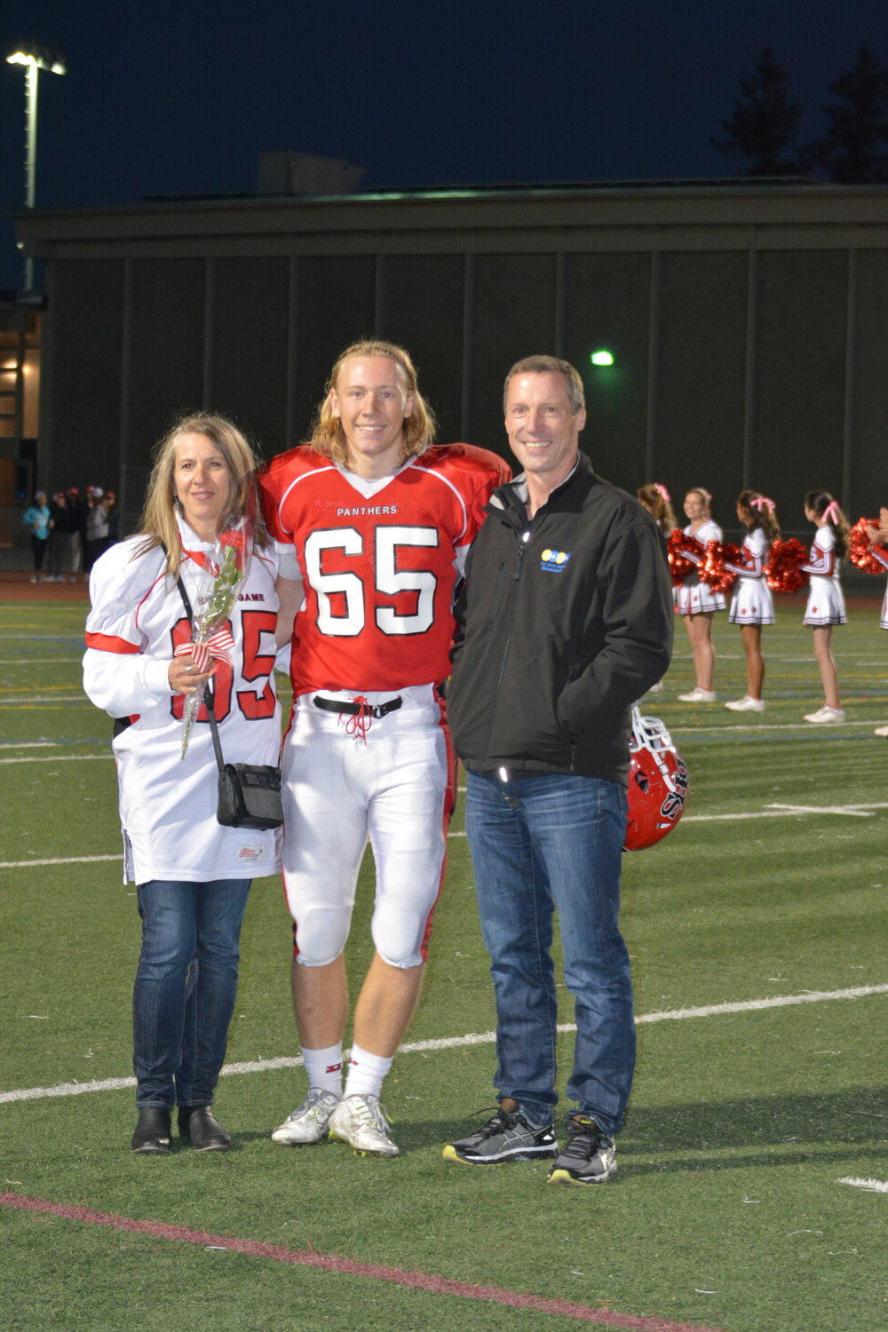 Lucas Flygare poses with his parents at the Senior Night game against Terra Nova High School.