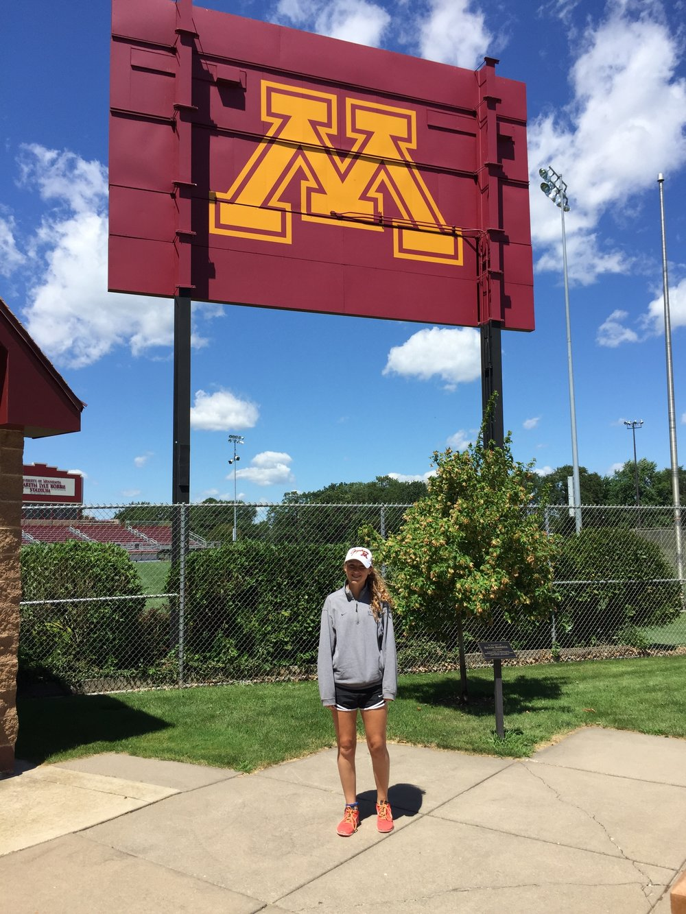 La Mond stands in front of the soccer field at the University of Minnesota.