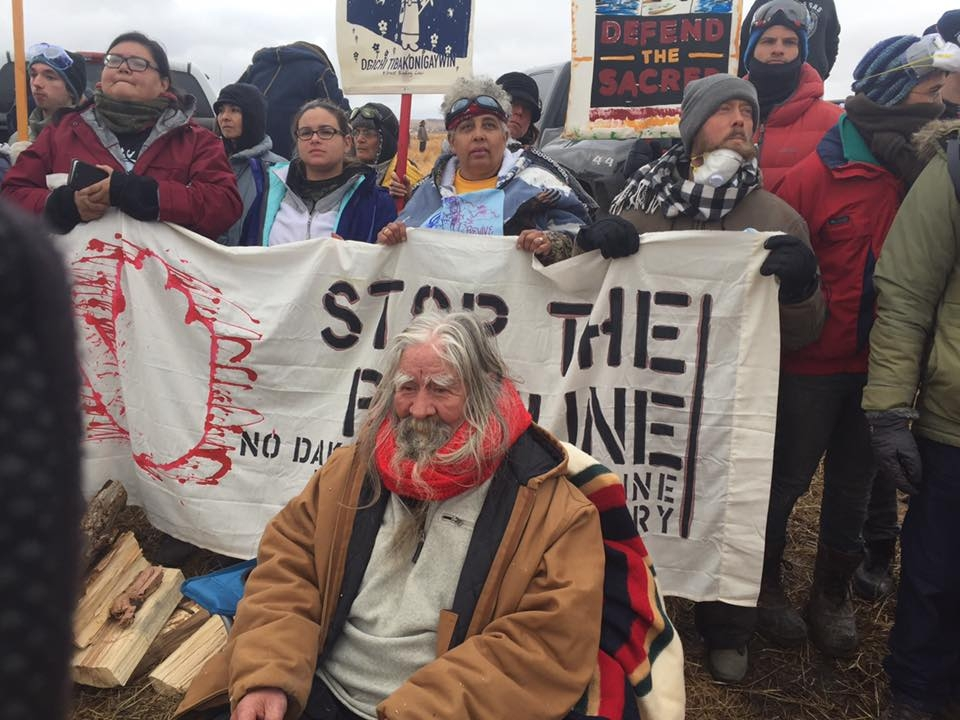 "Water Protectors holding up a sign that says ""Stop the Pipeline."""
