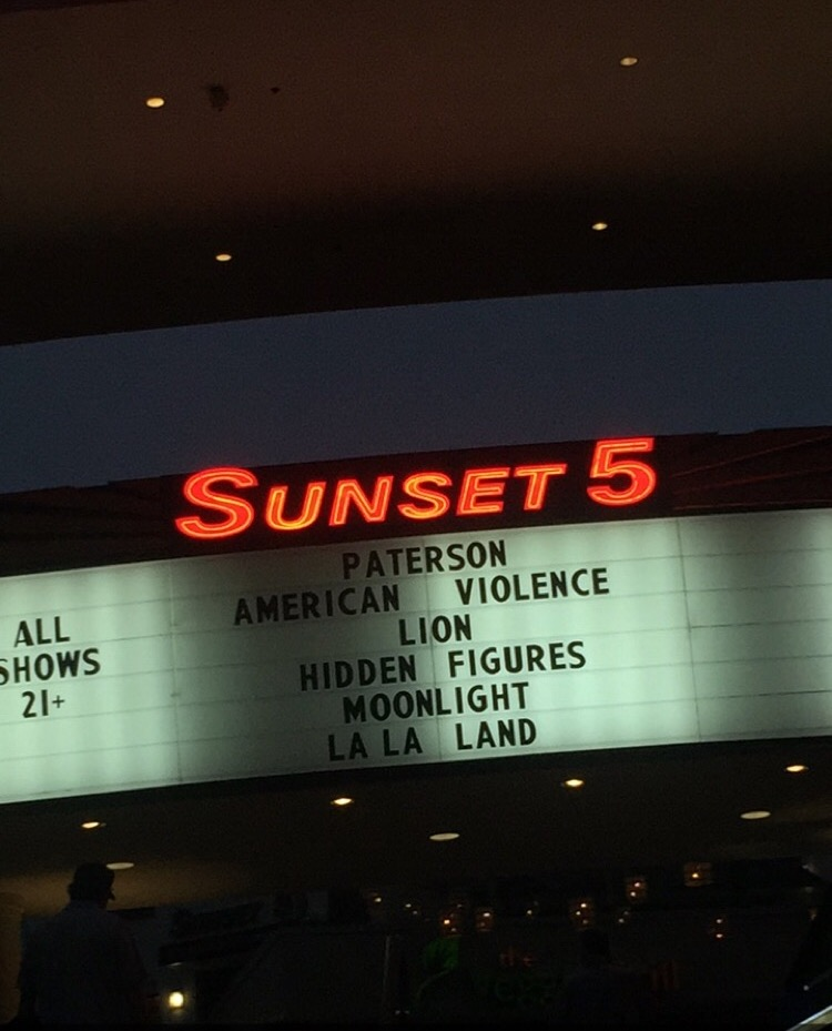 A movie theater in Los Angeles showing multiple films that have been nominated for this year's Academy Awards, including Lion, Hidden Figures, Moonlight, and La La Land.