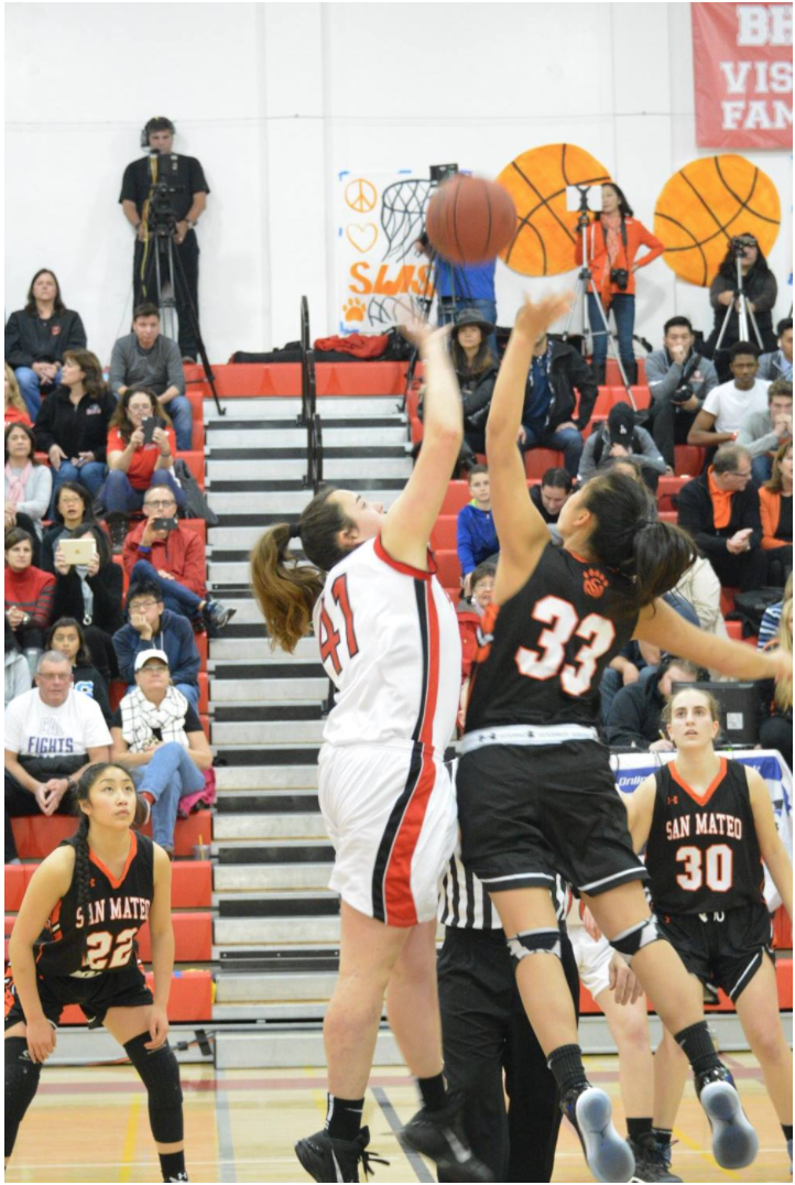 Junior Amber Moss jumps for the tip off in a regular season quad game against rival San Mateo High School.
