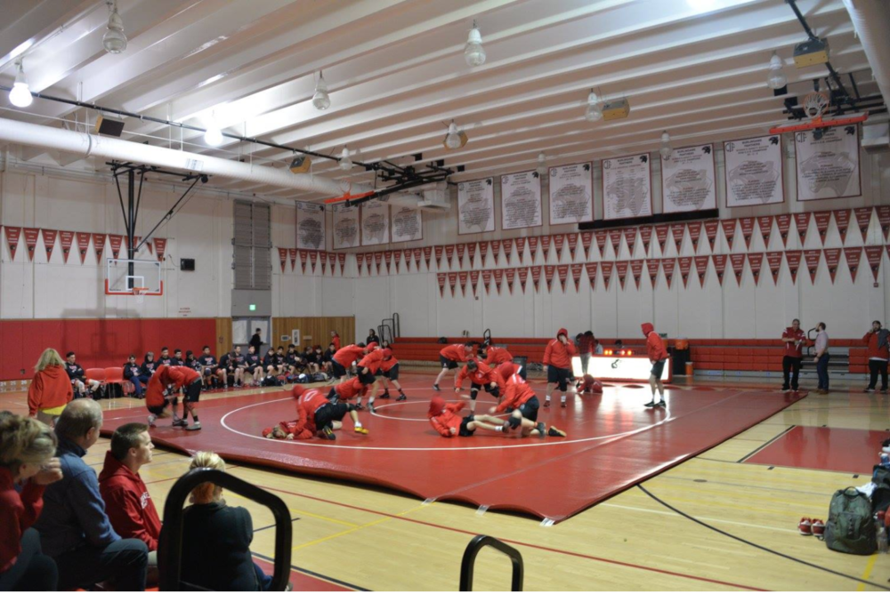 The wrestling team warms up for a regular season match earlier in the season.