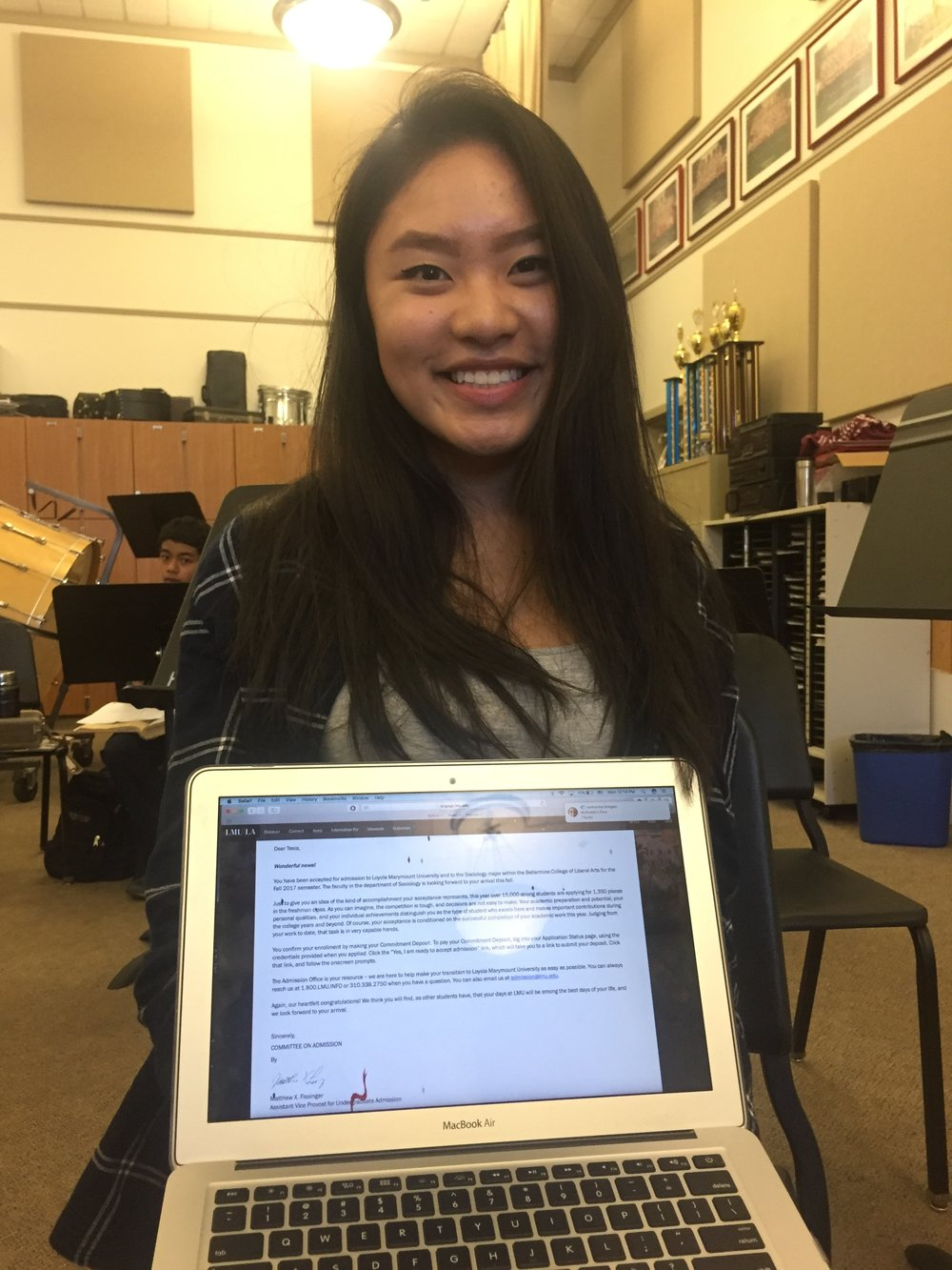 Senior Tesia Cheung holds up a letter of acceptance to Loyola Marymount University