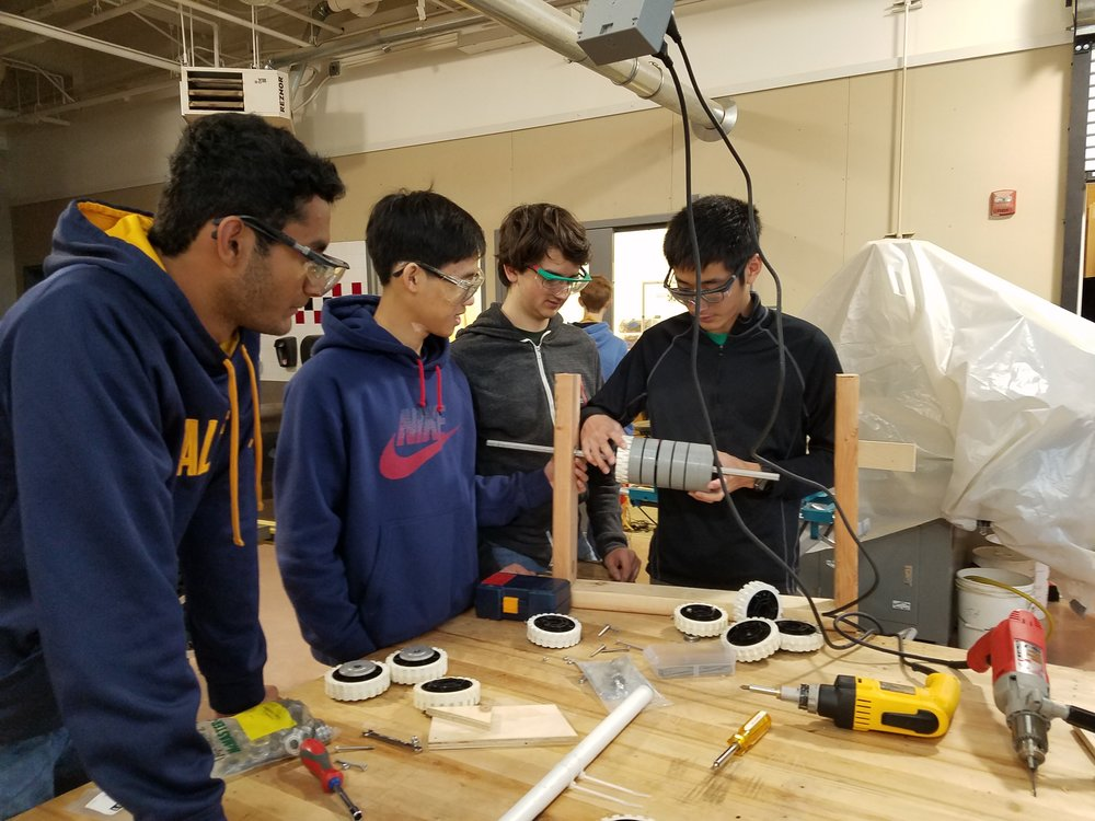 Junior Raja Poda, sophomore Junha Park, junior Robby Shield, and sophomore Darrion Chen (left to right) work on prototyping an intake system.