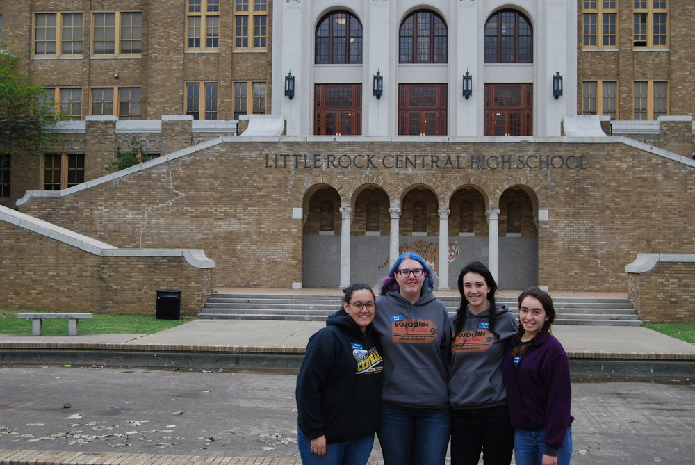 Junior Eileen Kohli poses with friends in front of Little Rock Central High School, which became a symbol of desegregation during the Civil Rights Movement.