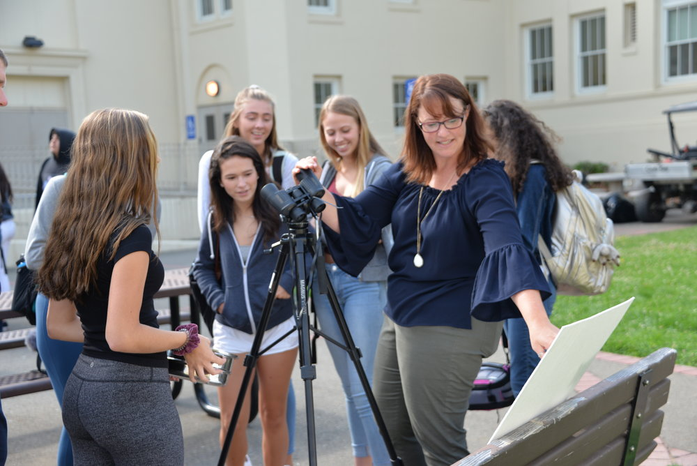 Science teacher Heather Johnson demonstrates to students a DIY solar viewing mechanism made using binoculars.
