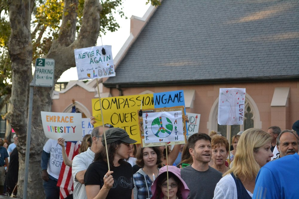 "Marchers carry signs as they make their way to Burlingame City Hall in the ""love Thy Neighbor"" peace march."