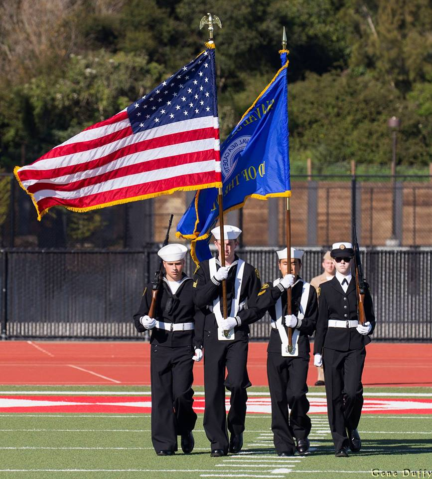Junior Lilli Hirth (far right) and three other Sea Cadets parade the colors during the national anthem at a college football game.