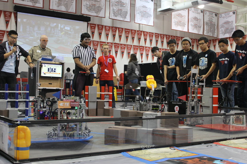 The teams RoboKnights and Kuriosity Robotics work together to place a yellow plastic relic outside the walls of the field in the final seconds of a match.