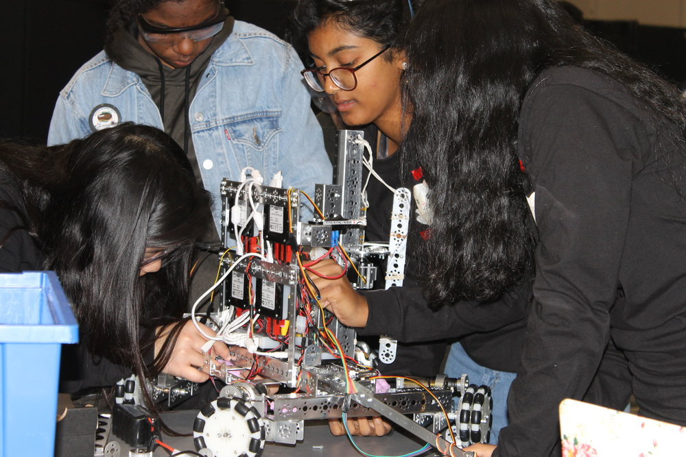Engineers on team 13223, the Lime Loops, fix their robot before the competition begins.