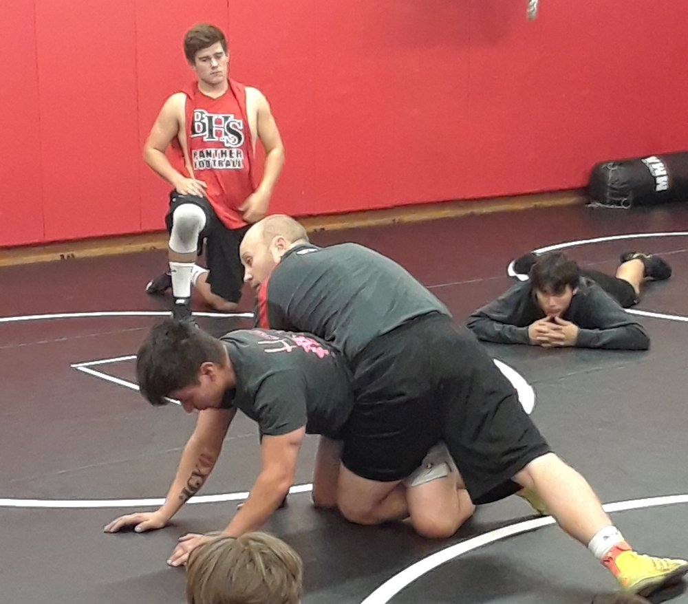 Assistant coaches Adam Bunzel and Ricky Condon demonstrate to wrestling members techniques and strategies to use during a match.