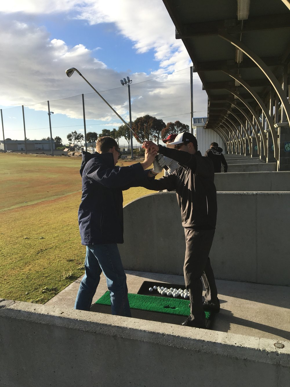 Coach of the boys golf team, Michael Zozos, teaches Brennan McDonald, a current sophomore, the correct swing position in the Burlingame CC course. Their next game is on March 6 against Menlo-Atherton at 3:00pm at Sharon Heights CC.