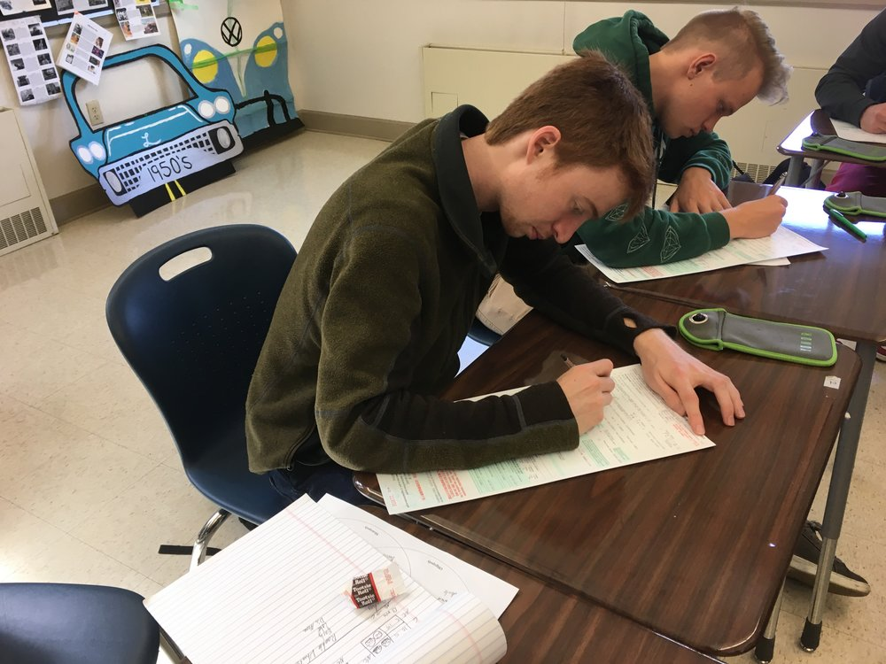 Seniors Max Schenk and Andrew Barrows fill out their voter registration form in Mrs. Liberatore's sixth period AP Mircoeconomics class on March 23- the Day of Student Registration to Vote.