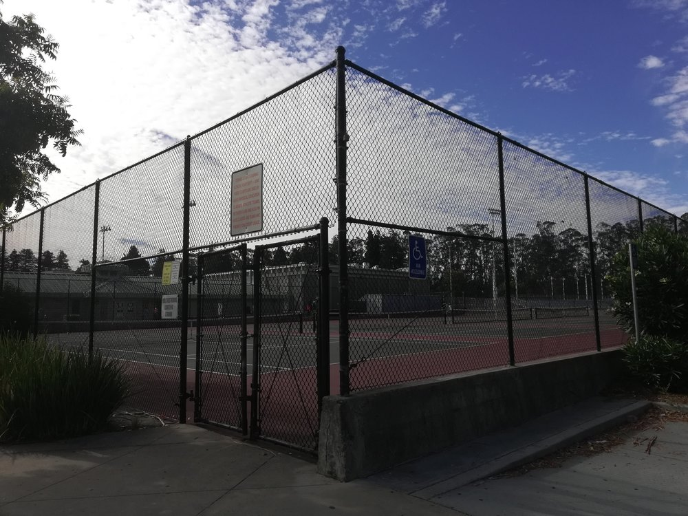 The tennis courts are enclosed by ten foot fences with locked gates.