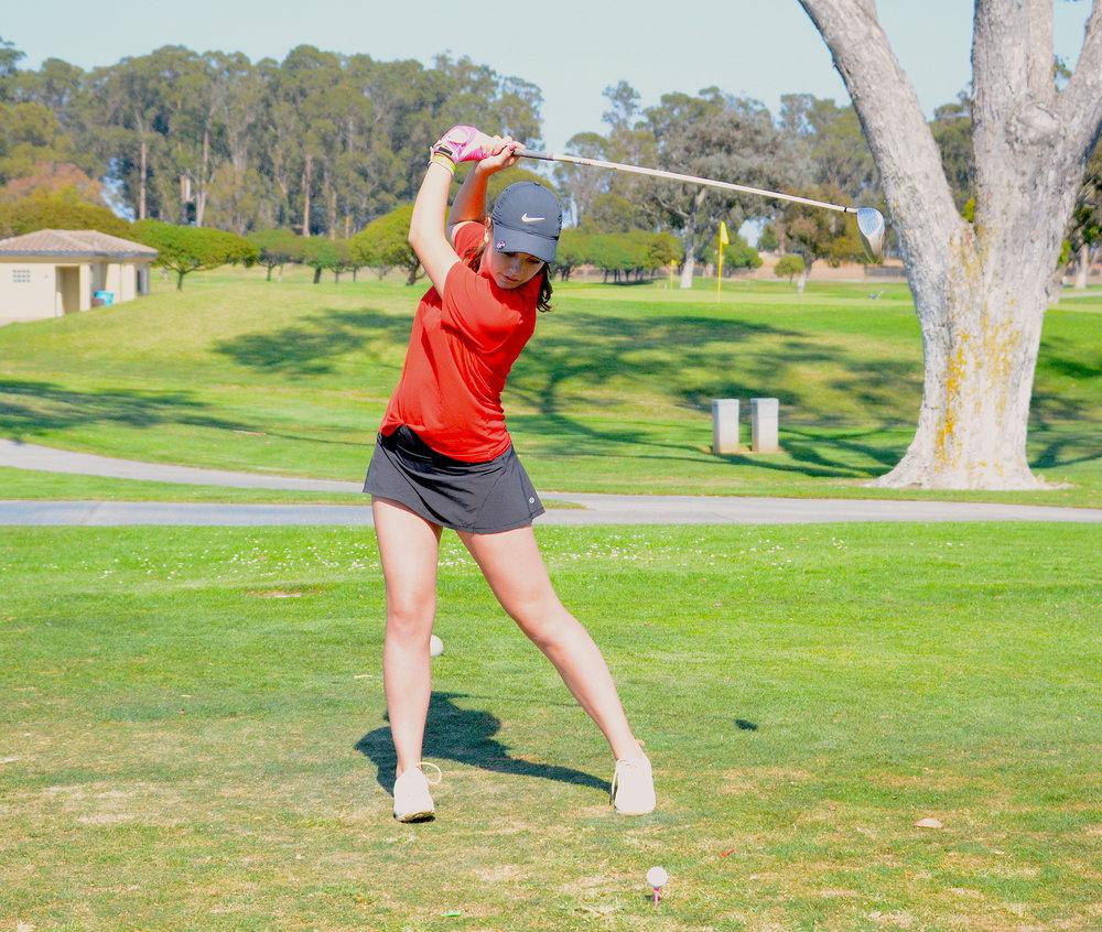 Senior Karina Mori prepares to strike a golf ball at the Popular Creek Golf Course at Coyote Point.