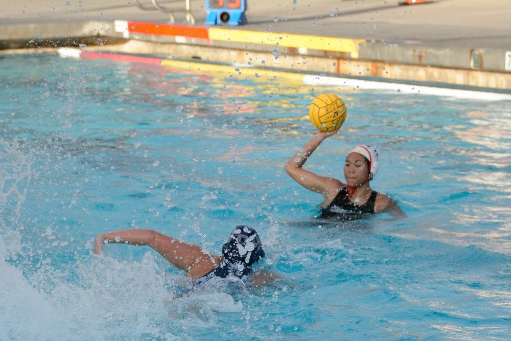 Junior Michele Tam grabs the ball as Carlmont player races towards her.
