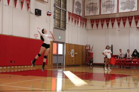 Senior Caroline Smith serves overhand towards the Westmoor High School team.