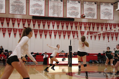 Senior Alexandra Edwards sets the volleyball while teammate Julia Everson, also a senior, prepares to spike the ball over the net.