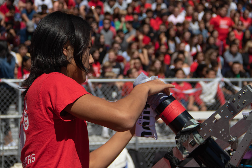 Junior Hubert Chen loads a T-shirt into the robotic's T-shirt cannon at the BHS Welcome Back rally.