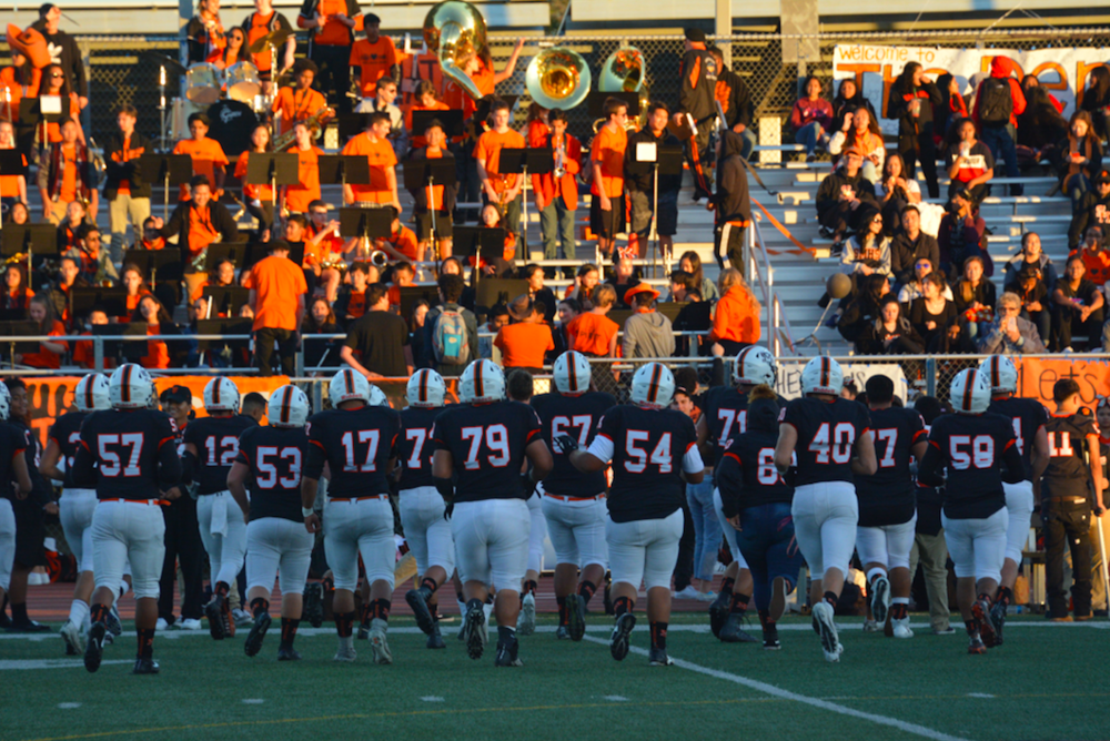 The San Mateo football team runs back to its bench for the final pregame huddle.