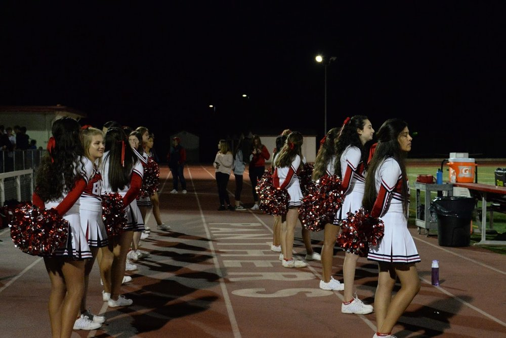 Varsity Cheer keeps a watchful eye on the field during the Varsity Football against Half Moon Bay on September 21st.