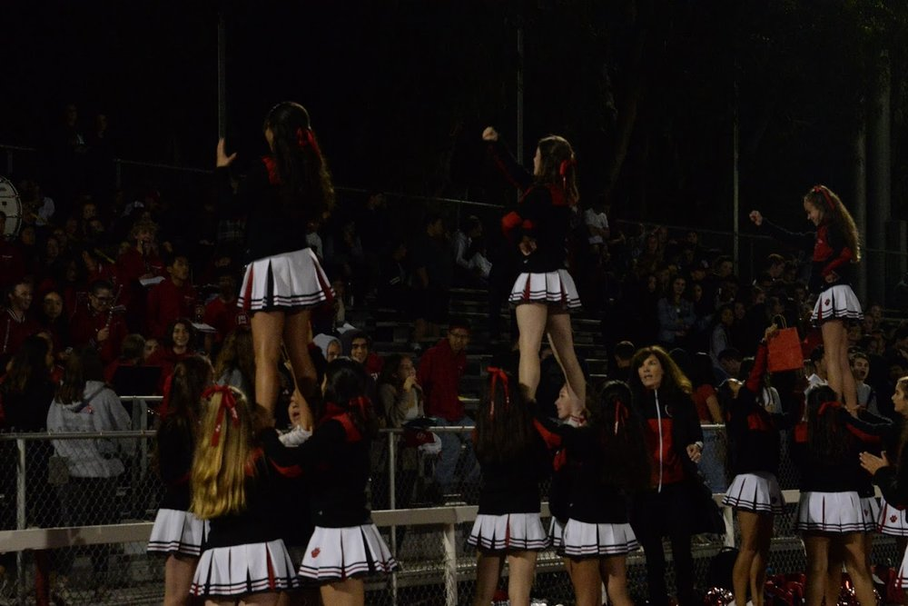 The cheer squad performs their halftime show in order to excite the crowd at the third home game of the season.