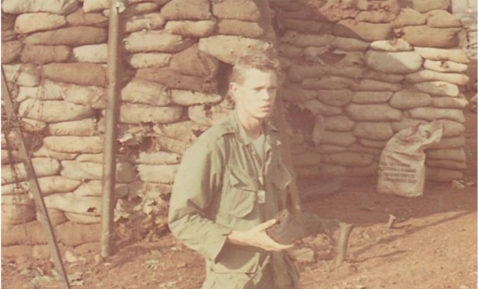 Skip Funk on day one of the Siege of Khe Sanh, January 21, 1968, standing in the crater of a 122mm rocket that just missed his bunker, seen in the background
