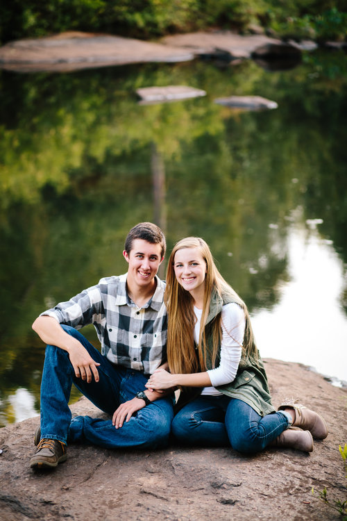 Young couple sits on rock by water engagement photography