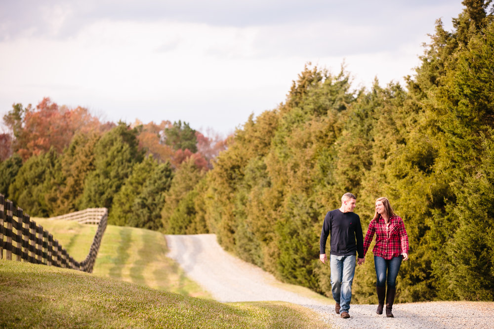Couple Walking On Country Road With Picket Fence