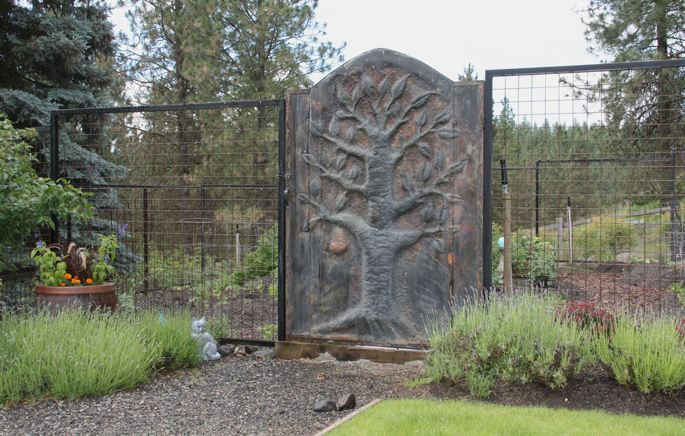 This metal garden gate was commissioned from a local artist and matches a larger gate at the driveway entrance.