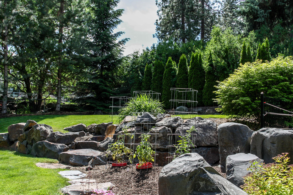 basalt boulder retaining wall with steps and vegetable garden