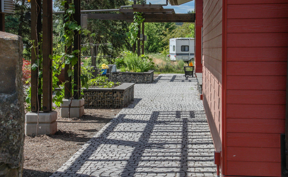pergola over stamped concrete pathway with gabion raised beds
