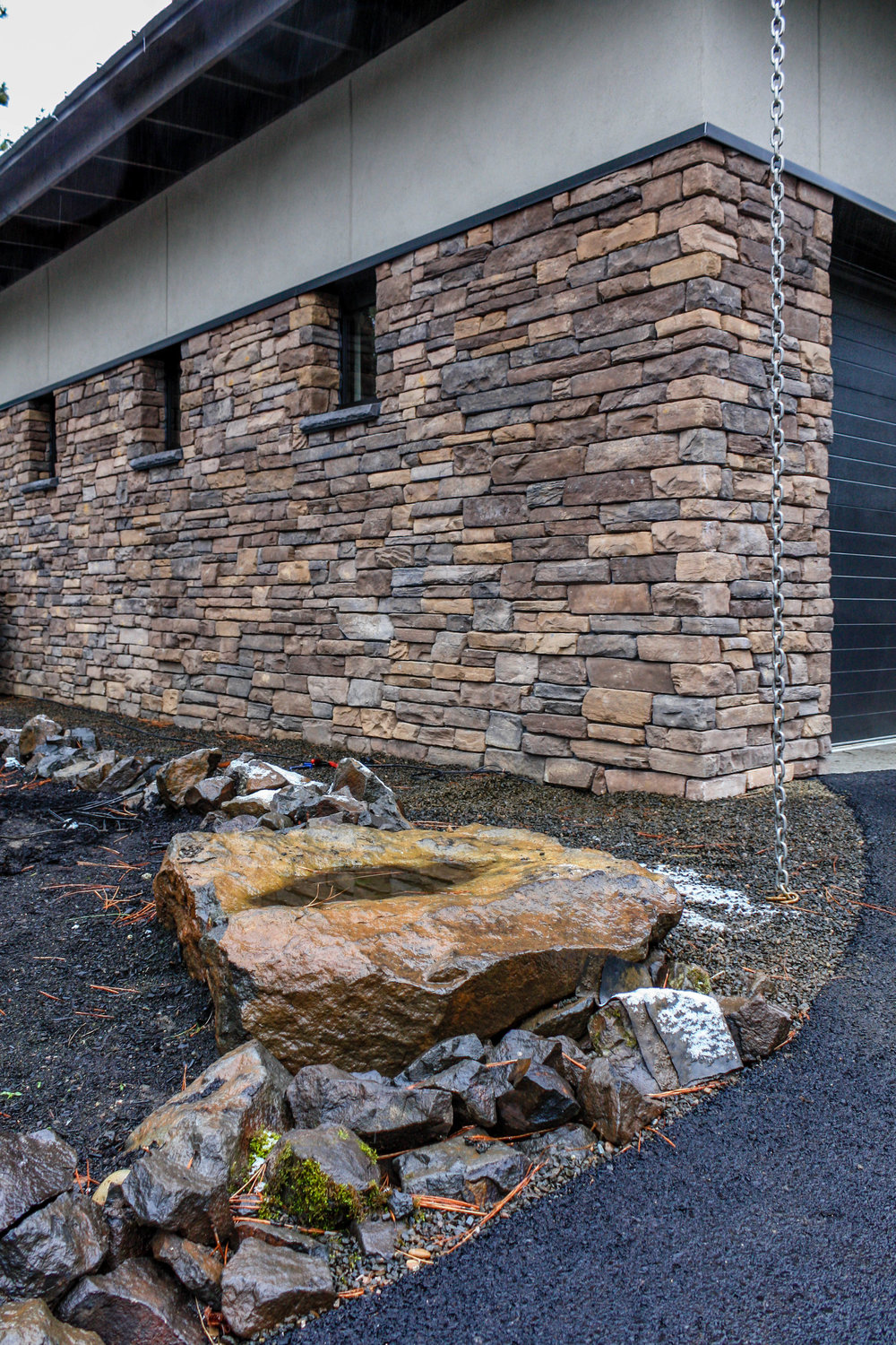 northwest contemporary landscaping with rain chain and rock work
