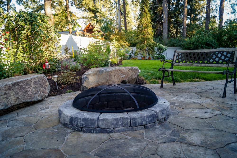 sunken fire pit and basalt bench rocks with belgard mega arbel patio in spokane landscape