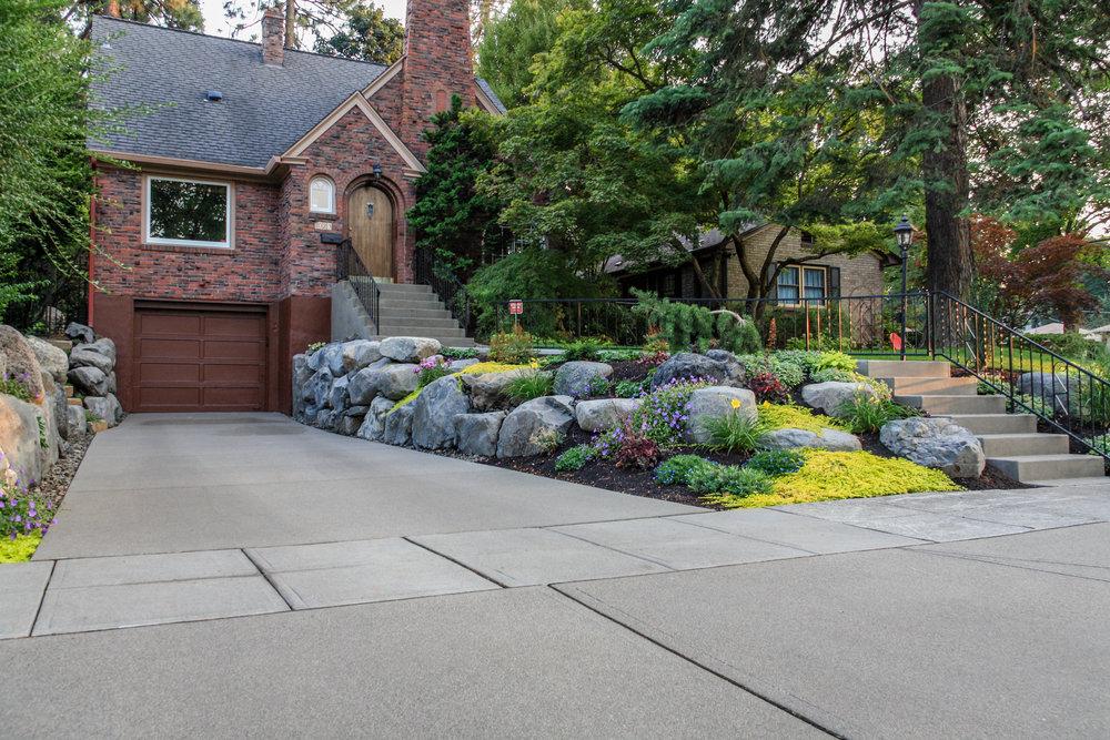 sandwashed driveway and boulder retaining walls