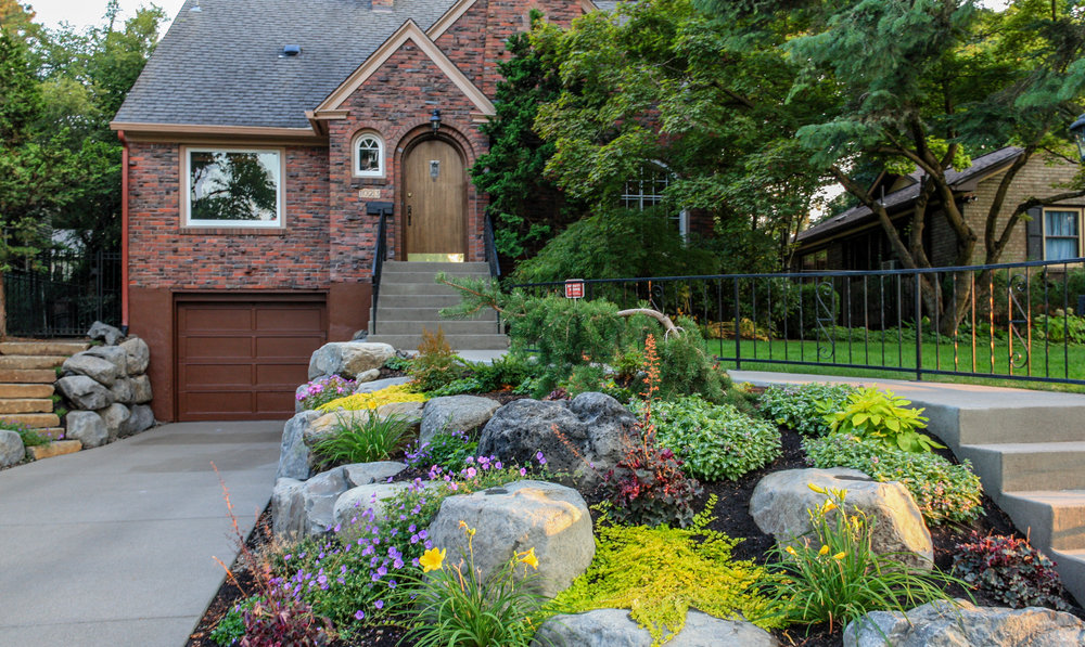 tudor brick bungalow with boulder retaining wall with rock garden