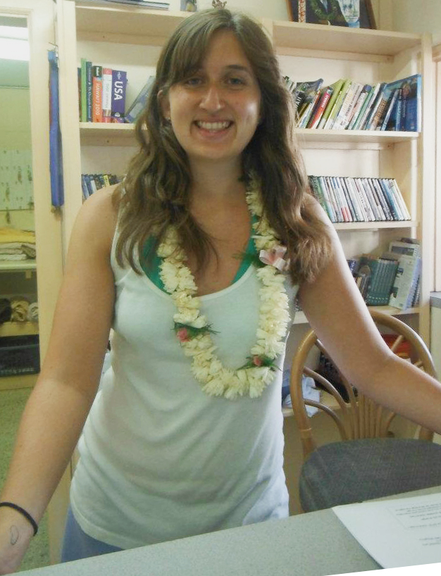 Jules working at the hostel reception in Hawaii wearing a Lei given to her by one of the guests.