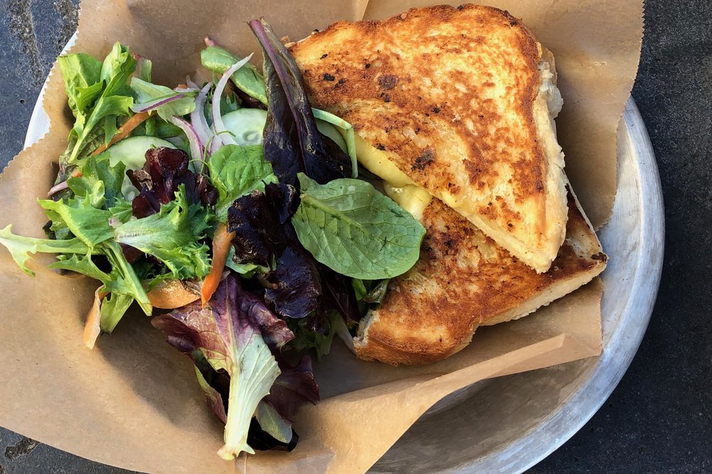 Grilled Cheese  Shelburne farms aged cheddar, Reid's Orchard apple, on house-made griddle pressed brioche. Served with a salad of mixed greens with an apple vinaigrette.