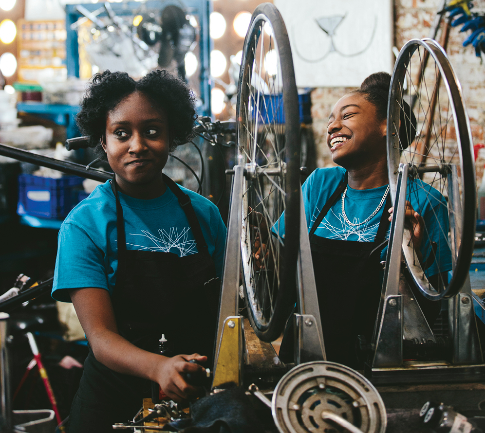 Nayla Hale (left), 16, giving someone some serious side-eye, and Khori Wilson, 13, repair newbies to master bike mechanics