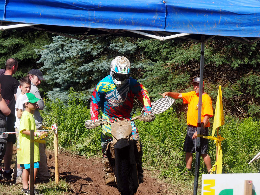 Billy Schlag takes the checkered flag for the winning Trail Pros team.