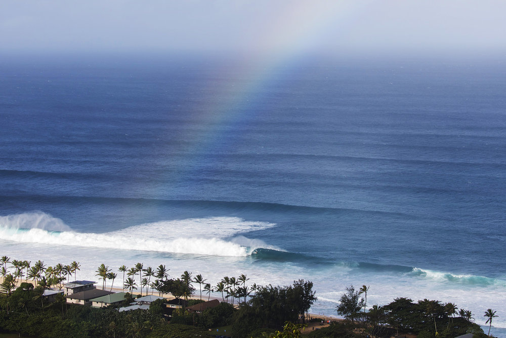 November 30th, 2017  On one of my last days in Hawaii, my friend Heath took me on a hike to get a better view of The Seven Mile Miracle. Just as this rainbow was disappearing, a second reef set came though and this unidentified surfer was in the perfect position for the wave of the day at Pipeline.