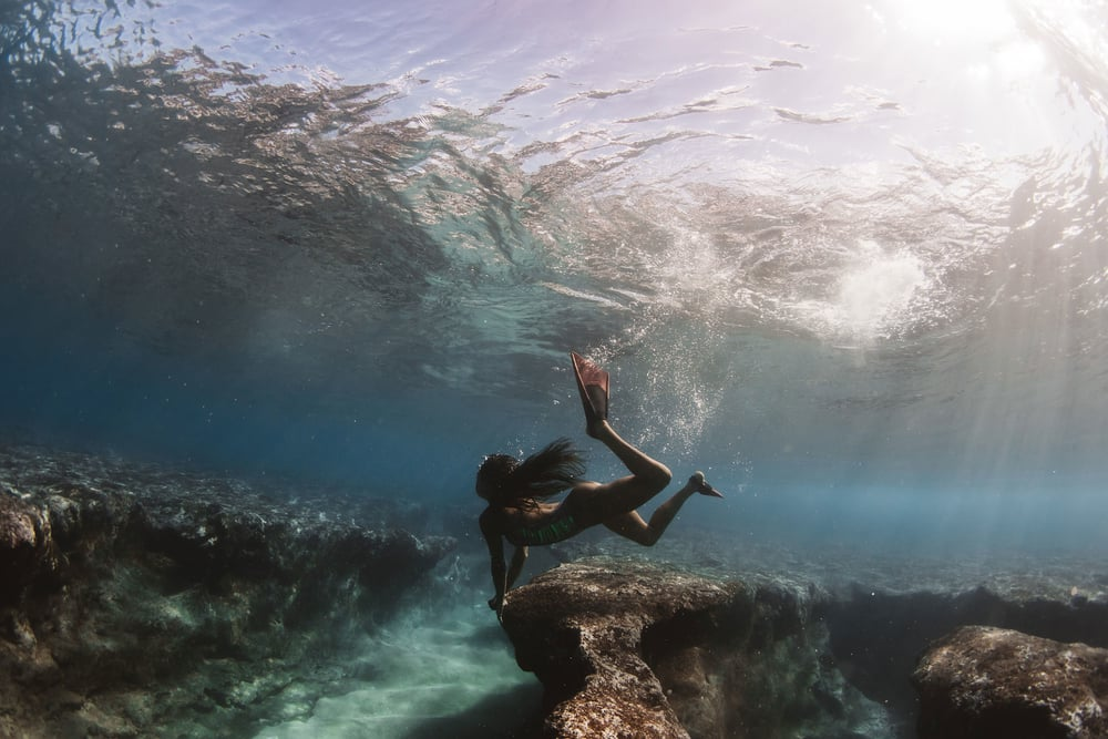 model holding onto reef at pipeline - ocean culture