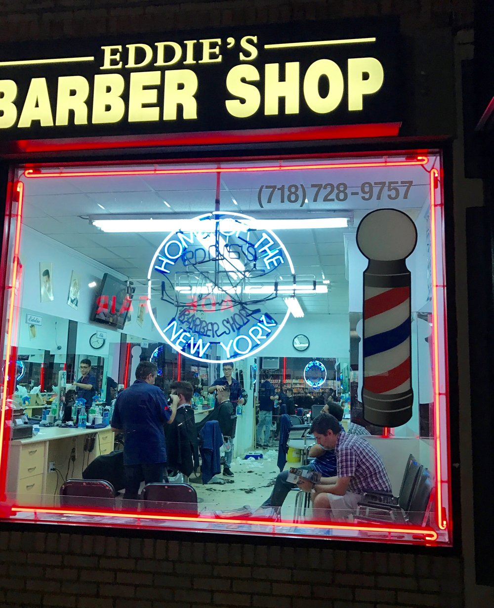 Barber Shop  I really like how the contrast between the cool florescent lights inside and the red neon on the edge of the window. The operator error here, though, is that I think this ought to be a straight shot of the window, with the neon lights lining up with the edges of the photo. I grabbed this as I was walking by, though, and I thought backing up to take that straight shot might be a bit too obvious or awkward with the people right inside.