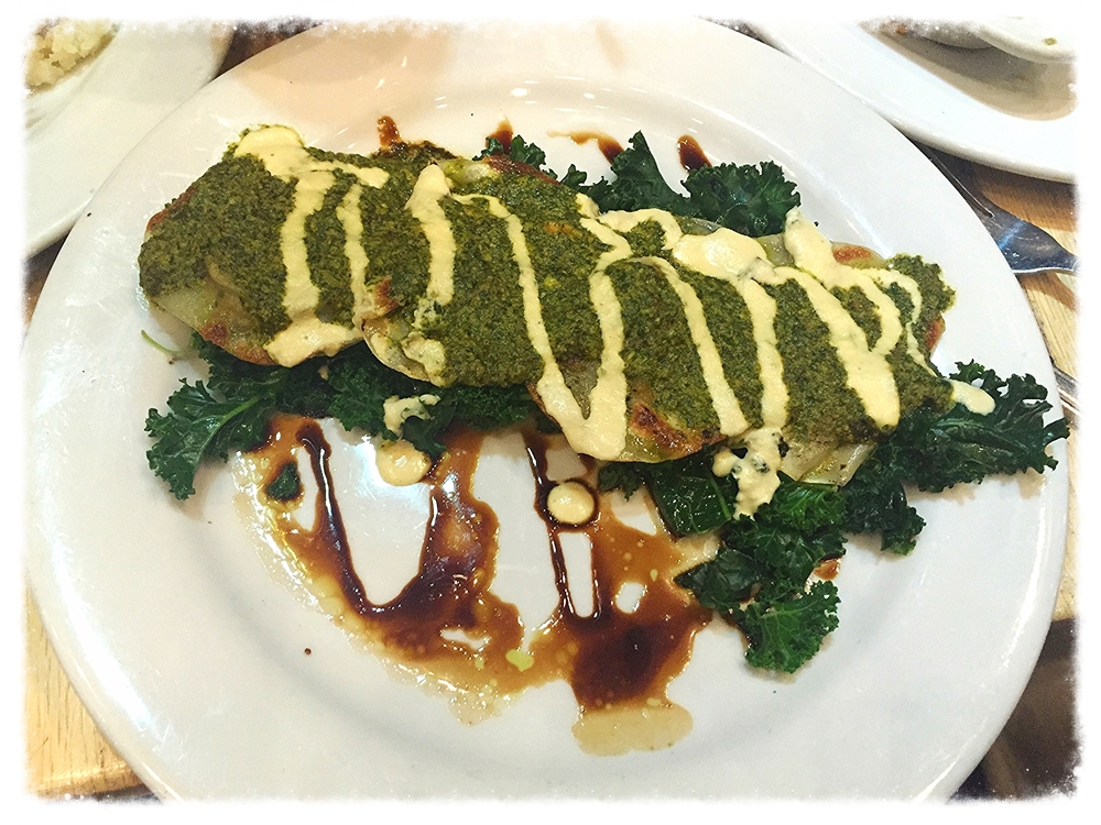 Butternut squash ravioli with pesto sauce and cashew alfredo over a bed of steamed kale
