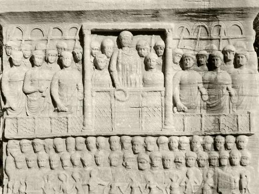 Base do Obelisco de Teosódio  Face oriental do pedestal, mostrando Teodósio oferecendo a coroa da vitória ao vencedor das corridas de bigas. O obelisco assenta sobre um pedestal de mármore com baixos relevos datados de quando o obelisco foi erguido em Constantinopla. Numa das faces, Teodósio é representado oferecendo a coroa da vitória ao vencedor das corridas de bigas; a cena é emoldurada com colunas e arcos coríntios, com espectadores alegres, músicos e e dançarinos que assistem à cerimónia. No parte inferior direita desse baixo relevo encontra-se um hidraulo (órgão hidráulico) de Ctesíbio; na parte esquerda encontra-se representado outro instrumento musical.      arquivo: 2005_08_08_DSC00968