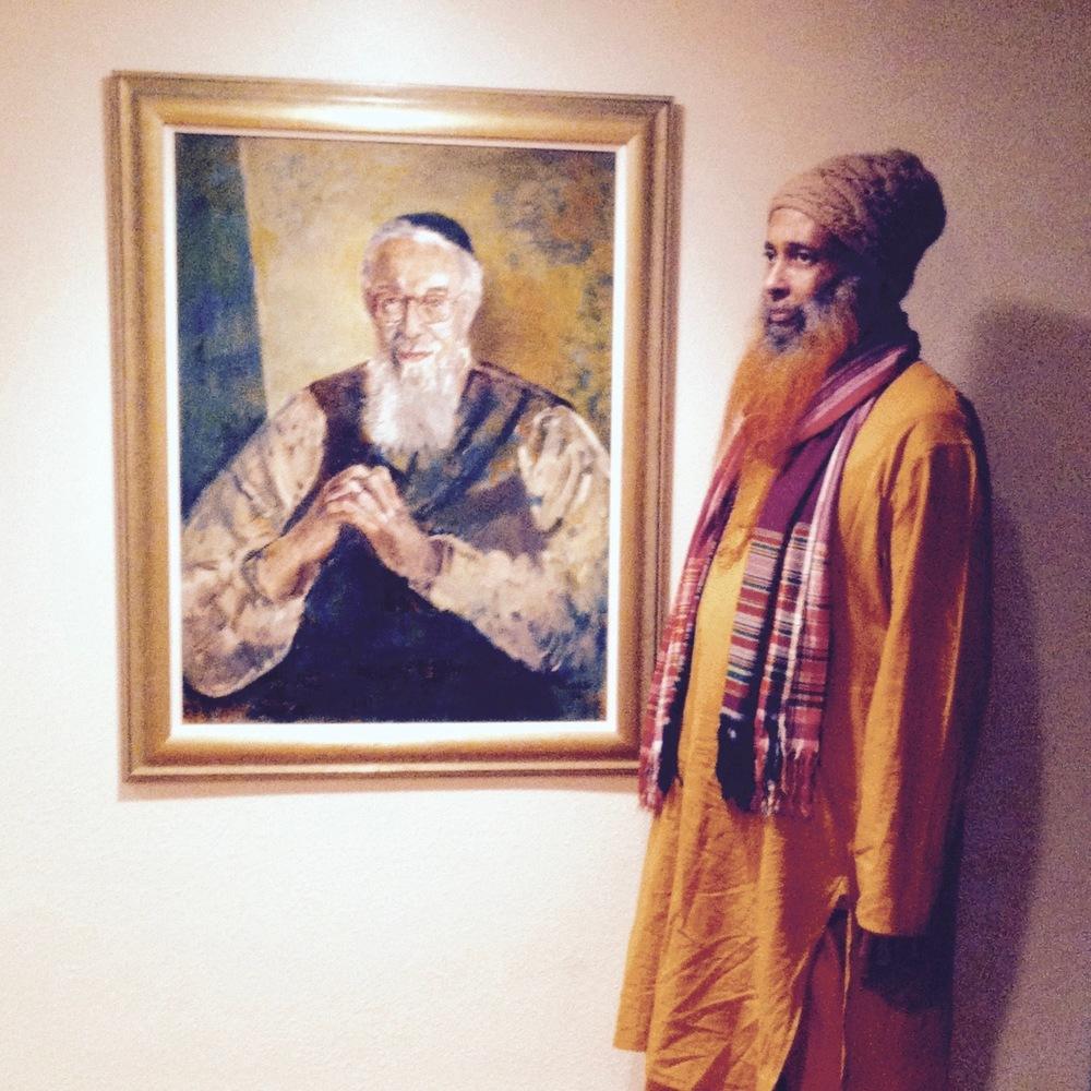 Ibrahim Baba next to a portrait of Reb Zalman in Rabbi Zalman Schachter-Shalomi's library. — Netanel Miles-Yépez, 2015.