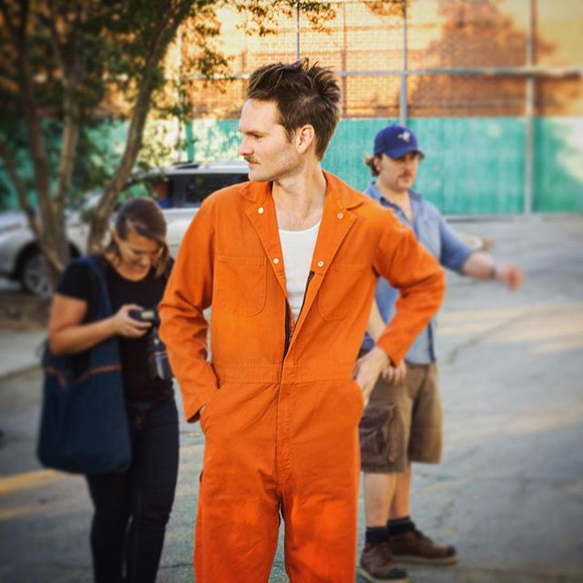 Tom Sawyer models his prison jumpsuit that was a couple sizes too small. #bandofrobbers #tomsawyer #bts #netflix #prison #jumpsuit @adamnee
