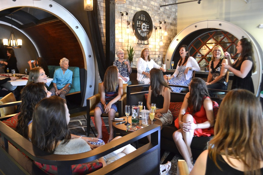 Guests having fun at bridal shower given at Hub 925 sitting in the Graffiti Tube, at the reclaimed wood bar and in the comfortable lounge area.