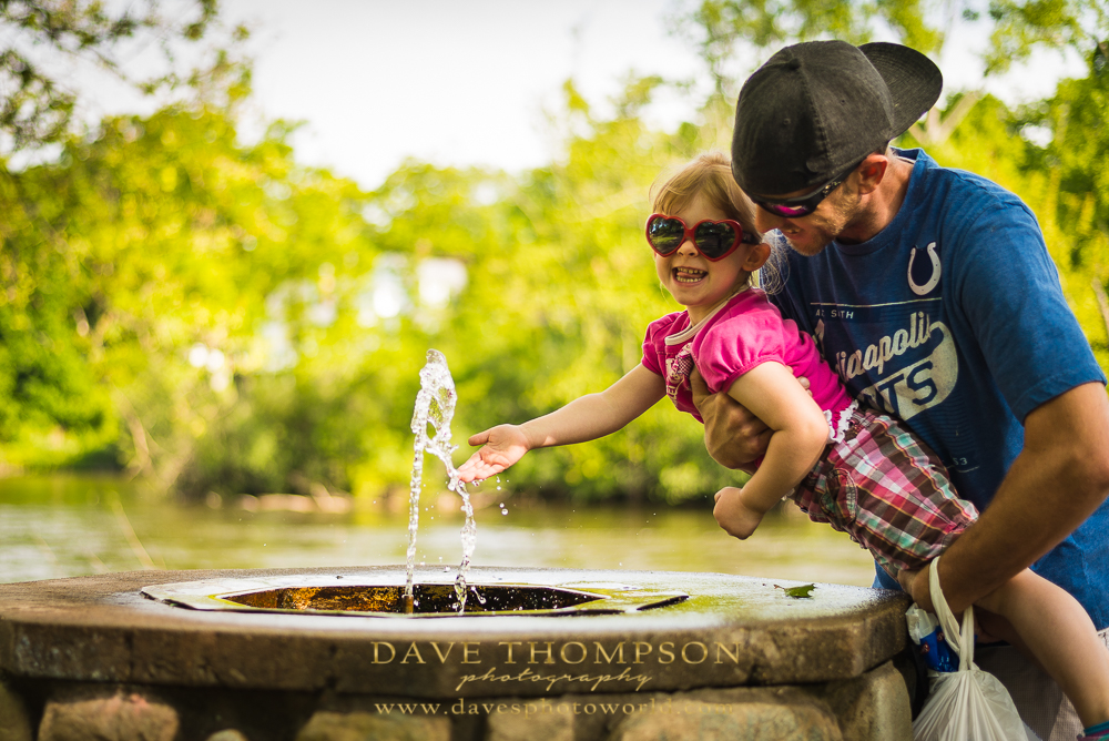 This little girl was really having fun drinking and playing in the water fountain!
