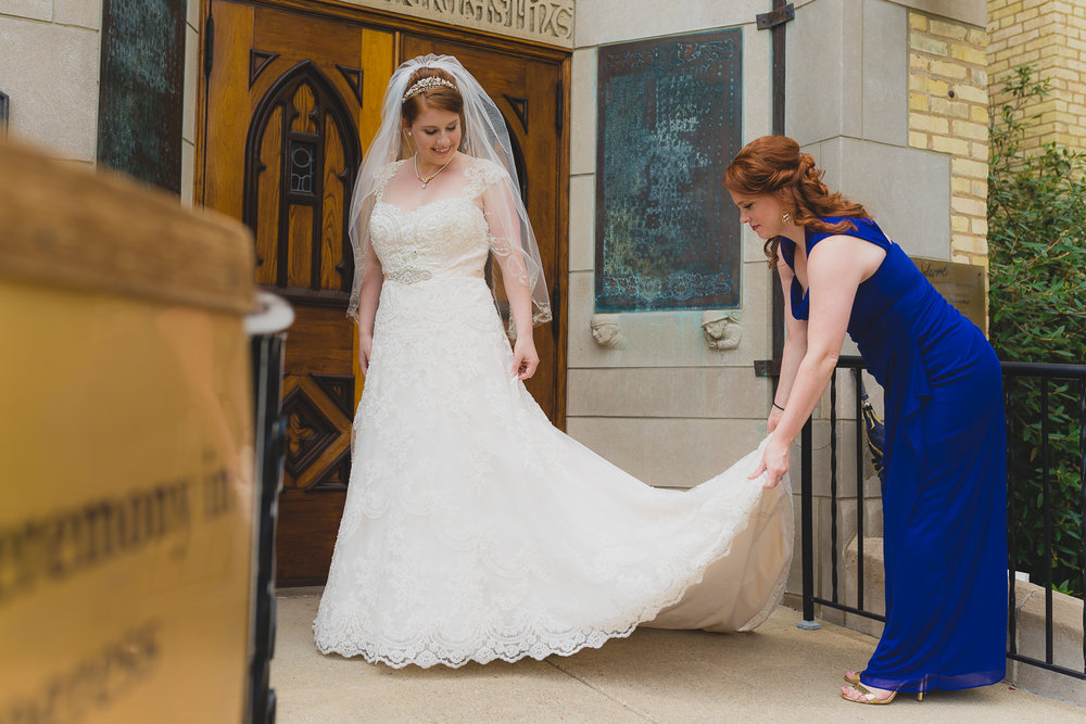 Sister helping with wedding dress